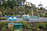 "Portmeirion, in North Wales, is a resort, where no one has ever lived. A self-taught Welsh architect named Sir Clough Williams-Ellis built it out of architectural salvage between the 1920s and 1970s, loosely based on his memories of trips to Portofino. Including a pagoda-shaped Chinoiserie gazebo, some Gothic obelisks, eucalyptus groves, a crenellated castle, a Mediterranean bell tower, a Jacobean town hall, and an Art Deco cylindrical watchtower. He kept improving Portmeirion until his death in 1978, age 94. It faces an estuary where at low tide one can walk across the sands and look out to sea. At high tide, the sea is lapping onto the shores. Every building in the village is either a shop, restaurant, hotel or self-catering accomodation. The village is booked out at high season, with numerous wedding receptions at the weekends. Very popular amongst the English and Welsh holidaymakers. Many who return to the same abode season after season. Hundreds of tourists visit every day, walking around the ornamental gardens, cobblestone paths, and shopping, eating ice-creams, or walking along the woodland and coastal paths, amongst a colourful assortment of hydrangea, rhododendrons, tree ferns and redwoods. The resort boasts two high class hotels, a la carte menus, a swimming pool, a lifesize concrete boat, topiary, pools and wishing wells. The creator describes the resort as ""a home for fallen buildings,"" and its ragged skyline and playful narrow passageways which were meant to provide ""more fun for more people."" It does just that.///A couple sit on park bench. Ornamental central gardens of Portmeirion village. Flanked by Dome Gallery, Gothic tower, Renaissance collonades, with lwans, flowerbeds, topiary, pools and fountains."