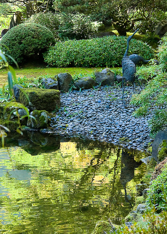 Heron sculptures reflected in upper pond of strolling pond garden (chisen kaiyu shiki niwa) in Portland Japanese Garden