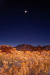 travel destinations: the sandia mountains desert twilight landscape glows beneath the moon rise, albuquerque, new mexico