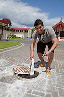 A Maori resident of Ohinemutu village removes a small sack containing two ears of corn (maize) he has just cooked in the boiling hot spring water just under the surface of the paving stones in the plaza in front of the Maori meeting house, rear right.  Rotorua, north island, New Zealand.