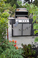 Backyard BBQ grill upscale for outdoor cooking on patio, with skewers kabobs of tomatoes and mushrooms, flower garden with plants and vegetables