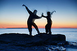 Two blurred silhouettes of people practicing martial arts at dusk in the nature over colorful twilight sky