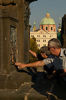 Czeck Republic, Prague, Visitors on the Charles Bridge reach out to rub the plaque of the patron saint of the country, Jan of Nepomuk. Legend has it that you will one day return to Prague if you touch the plaque.