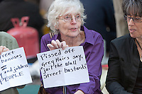 A woman holds a protest sign in Zuccotti Park reading *Pissed off grey hairs say, jail the Wall Street bastards* during the Occupy Wall Street demonstration in New York City, New York.