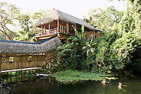 Tourists swimming at the Reserva Ecologica de Nanciyaga, an ecological reserve and ecolodge on Laguna Catemaco, Veracruz, Mexico