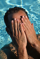 Man covering his face while in a swimming pool