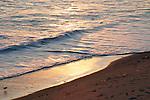 Waves breaking on shore at sunset in Malibu, California, USA