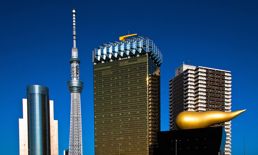 A row of buildings against a blue sky showing example of Tokyo`s varied & distinctive architecture.Includes Tokyo Sky Tree,Asahi Super dry Hall - topped with a huge golden object d`art, Asahi Beer Tower (the amber colored glass building) & Sumida Ward Office.