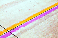 Yellow and purple lane markers on an airport runway.
