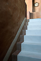 The illusion of a stair carpet has been created by using a satin-finish white paint in contrast to the rough finish of the walls and floor