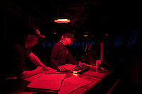 Coast Guard crew members work under red lights at night on the bridge of the icebreaker Healy.