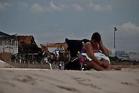 A woman takes a sun bath next where a massive fire that engulfed dozens of businesses along a boardwalkin in Seaside Park September 13, 2013 by Kena Betancur / VIEWpress