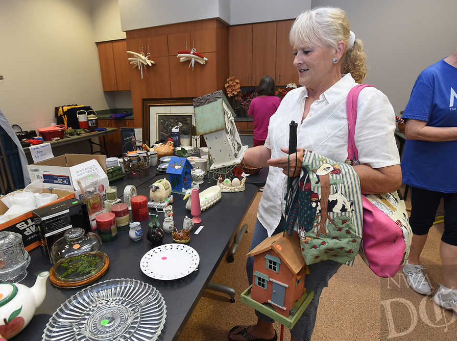 NWA Democrat-Gazette/FLIP PUTTHOFF <br />BARGAIN BIRD HOUSE<br />Betty Sewall of Bella Vista ponders the purchase of a bird house Wednedsay May 17 2017 at the annual Rogers Adult Welness Center rummage sale. Items of all types are on sale at the center, located at 2001 W. Persimmon St. Profits fund various programs at the center. The sale runs through noon Saturday.