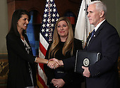 United States Vice President Mike Pence shakes hands with Nikki Haley after swearing in Haley as the U.S. Ambassador to the United Nations January 25, 2017 in Washington, DC. Haley was formerly the Governor of South Carolina. Also pictured is a member of Haley's staff, Rebecca Schimsa. <br /> Credit: Win McNamee / Pool via CNP