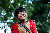 Young burmese village girl, giggles in a bamboo forest