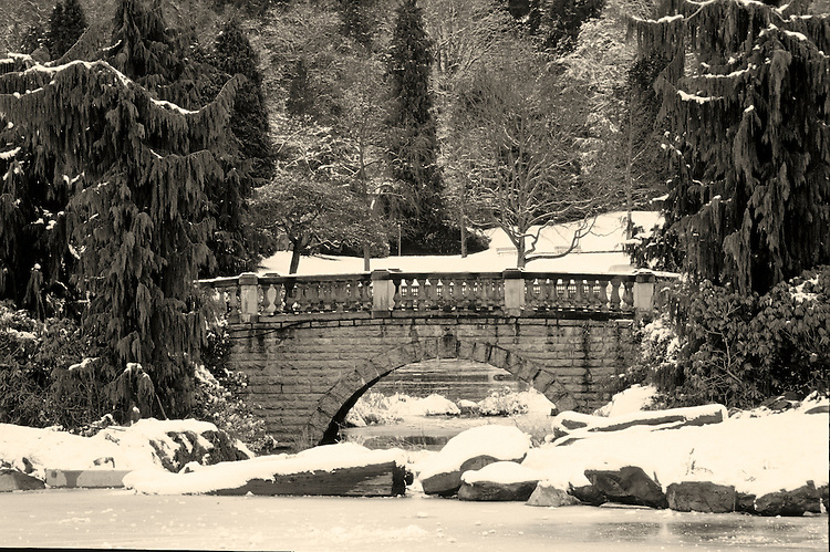 Stone bridge walkway leading into Stanley Park, surrounded by trees, rocks and ice after snowfall, Vancouver, BC.