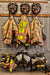 Three firefighter uniforms hanging on the station wall HDR