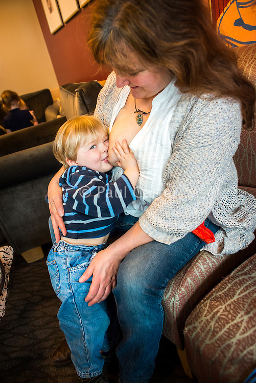 A woman breastfeeds her two year old toddler in a coffee shop. The little boy is standing up and smiling at the camera.<br /> <br /> Image from the &quot;We Do It In Public&quot; documentary photography project collection: <br />  www.breastfeedinginpublic.co.uk<br /> <br /> Dorset, England, UK<br /> 17/04/2013