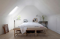 """A the foot of the bed in the master bedroom is an antique """"os de mouton"""" banquette made of grey oak and covered in natural linen"""