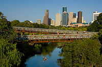 Stock photo of the Houston skyline from Buffalo Bayou with Rosemont Bridge and kayaker