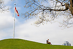 A woman sitting in a public park, reading outdoors in Vancouver, British Columbia