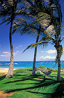 A vacationer in a hammock at Ulua beach, Wailea, Maui, with a view of the island of Lanai