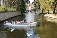 Tourist boat on canal outside Begijnhof, Bruges; Belgium; Europe