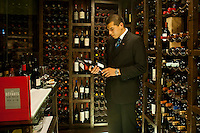 José Miguel Burga, sommelier of Central, selects a bottle of wine at Central's cellar.