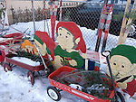 Plywood elves sit behind vinatage red wagons while wooden skis rest against a chain link fence