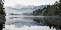 Misty dawn at Lake Matheson with rainforest and Southern Alps, Westland Tai Poutini National Park, UNESCO World Heritage Area, West Coast, New Zealand, NZ