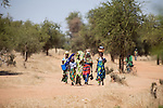 """In West Africa, certain villages have markets that """"assemble"""" at regular intervals, such as weekly or every three days.  People from villages around the region come on market day to buy and sell food, livestock, and other goods and services.  Here, a group of women and children arrive by foot at the village market of Bourro in northern Burkina Faso."""