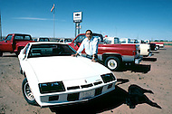 May 6th to 13th, 1985 in Navajo Reserve, AZ. Donald Davis, a local Chevrolet dealer In Tuba City, AZ. He is posing next to a Camero sport car which has very few chances of being sold in Navajo since they always prefer pick up trucks.