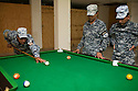 """Iraqi policemen shoot pool at the headquarters of the 5 Division 2nd Brigade Iraqi Federal Police August 25, 2010 in Baghdad, Iraq. Much of the headquarters contains items such as the pool table, AC's, and sandbag security walls, which were left behind by American units who once commanded the base and have now been """"inherited"""" by the Iraqi security forces.   ."""