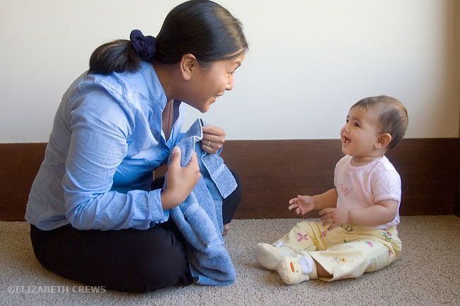 Berkeley CA Nepalese mother playing peek-a-boo (object permanence) with seven-month-old baby girl MR