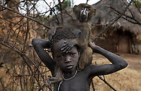 A local child paints the face of his monkey hoping to earn a few tourists dollars if he is photographed. Influence from outside people changes the culture from one of pride in customs to one of begging or demanding to be paid.
