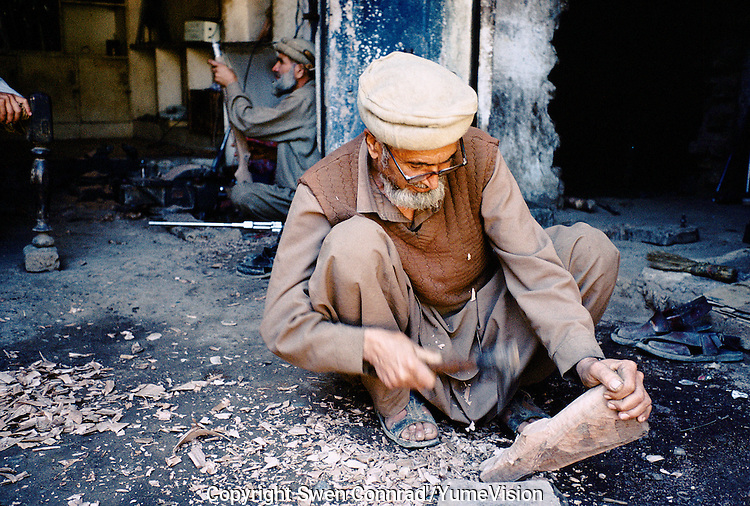 A old men making Butt for new made Pakistani Kalashnikovs. Darra town in Pakistan clandestinely provides arms to more than eight Central Asian countries.