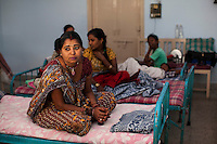 Shakku (center), an ex-surrogate, used to work as a hard labourer making daily wages lower than the minimum wage, in construction sites and as a domestic servant, sits amongst other current surrogates in the surrogate's hostel at the Akanksha Infertility Center in Anand, Gujarat, India on 12th December 2012.  Photo by Suzanne Lee / Marie-Claire France