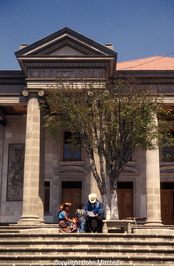 Mayan family sitting on the steps of the neoclassical style Teatro Municipal or Municipal Theatre in the city of Quetzaltenango, Guatemala