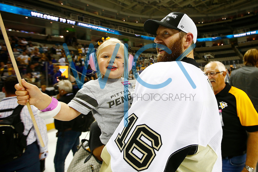 Eric Fehr #16 of the Pittsburgh Penguins holds his daughter following their 3-1 win against the San Jose Sharks during game six of the Stanley Cup Final at SAP Center in San Jose, California on June 12, 2016. (Photo by Jared Wickerham / DKPS)