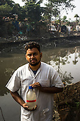 29 year old Bicky Dome, a laboratory assistant from the Institute of Serology poses with a bottle of collected sewage samples in Kolkata, West Bengal, India.