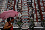 A woman walks home near the Olympic Games venues in Beijing, China on Monday, August 4, 2008. The building behind her received a new paint job last month. The city of Beijing is gearing up for the opening ceremonies of the Olympic Games.  Kevin German