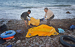 The body of a refugee child is collected from a beach on the Greek island of Lesbos on November 1, 2015.  It was covered with a plastic raincoat by Spanish lifeguards until it could be picked up by local authorities.  The body appeared to be that of an Afghan boy of about 8 years of age. Thousands of refugees have died this year attempting to cross the Aegean from Turkey to Greece. Fleeing violence in Syria, Iraq, Afghanistan and elsewhere, most are on their way toward western Europe.