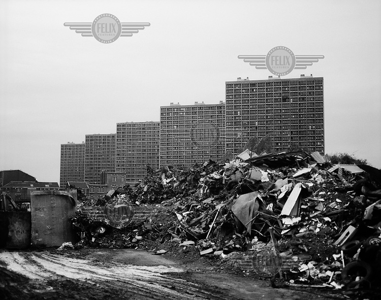 A heap of rubble in front of a row of high rise apartment blocks.