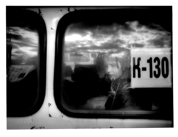 Girl Gazes from Back Window of Minibus, near St. Petersburg, Russia.