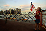 A young girl with flag looks back as she and her family take a ferry from Lower Manhattan after stopping to see what remains of the Twin Towers just days after the 9/11 attacks.