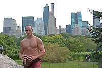 Shirtless twenty something year old man in holding a football in Central Park New York City