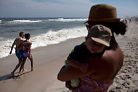 Long Beach Island, NJ - June 29, 2013 :  Jessica Cannatora with her son Michael Cannataro, 9 months, from William Park, NJ, watch the waves at Beach Haven on Long Beach Island, NJ on June 29, 2013. People are returning to the beaches for the summer after recovery efforts post super storm Sandy.