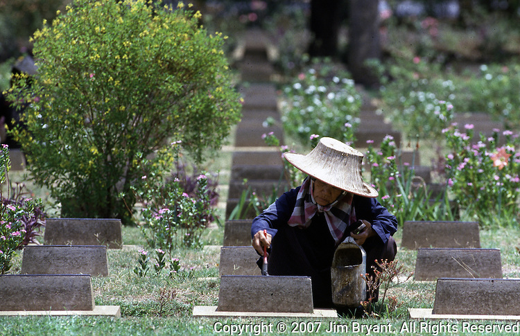 A Thai worker uses a brush to clean headstones in a cemetery filled with the graves of nearly 7,000 Australians and Englishmen who died  during World War II in Kanchanaburi, Thailand. Over 16,000 allied P.O.W.s died of starvation, maltreatment and disease while building the bridge on the River Kwai and a 250- mile railway from Thailand into Burma. The Bridge on the River Kwai, known to many P.O.W.'s as the bridge of sorrow, attracts thousands of tourists yearly. (Jim Bryant Photo).....