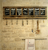 A series of blackboards for each day of the week act as an 'aide memoire' against the stone wall of this kitchen
