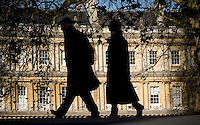 Views of The Circus, Bath, with couple walking through, silhouetted  against the buildings and trees.